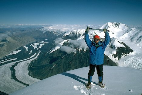 Photo of excited woman mountain climber on the summit