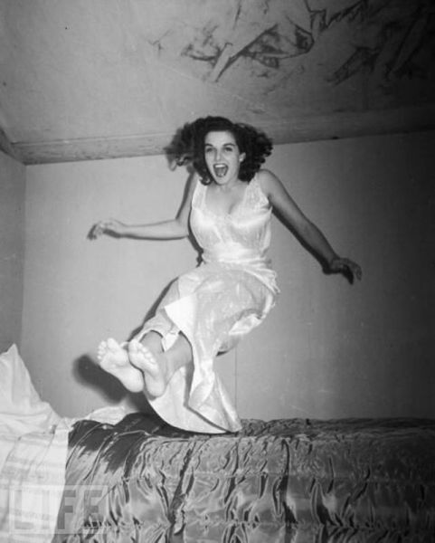 Woman bouncing on bed